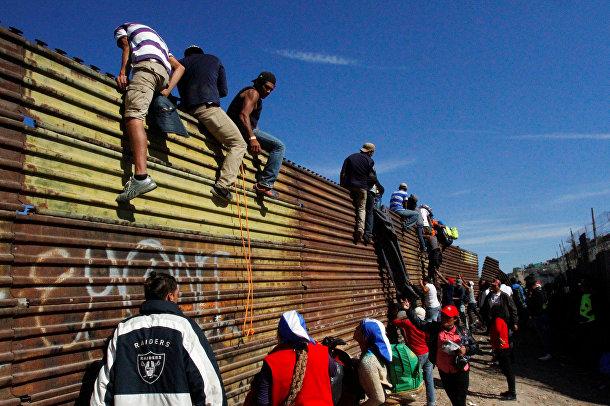Нелегальные мигранты пересекают границу в Тихуане, Мексика