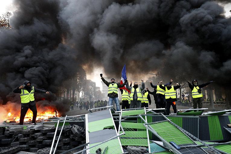 Участники акции протеста против роста цен на бензин «желтые жилеты» в Париже