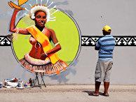 Местный художник наносит последние штрихи на фреску в рамках подготовки к форуму АТЭС в Порт-Морсби