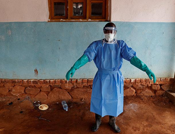 Медицинский работник в защитном костюме в больнице для больных Эболой в Бвана-Сури