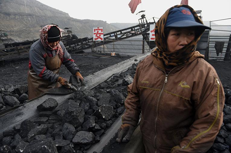Рабочие сортируют уголь возле угольной шахты в Датуне, Китай