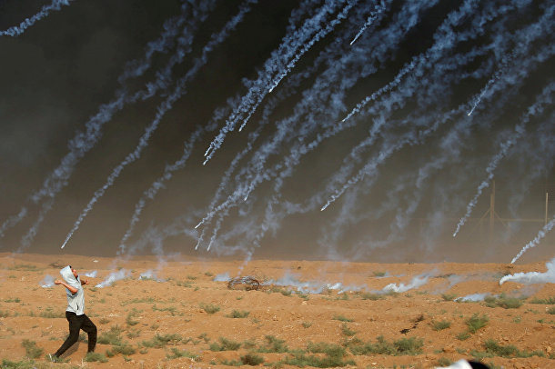 Палестинский демонстрант бросает камни в израильские войска во время акции протеста у пограничного ограждения между Израилем и сектором Газой