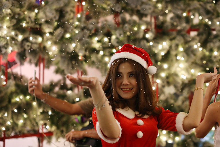 Женщина позирует с рождественскими декорациями