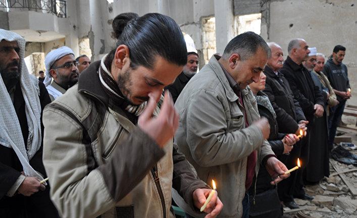 Христиане во время молитвы в церкве в городе Дейр-эз-Зор, Сирия