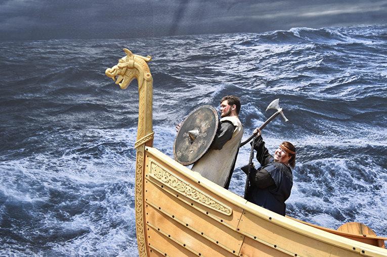 Люди позируют в образе викингов на макете драккара
