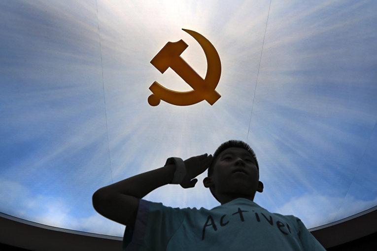 Ребенок у логотипа Коммунистической партии в военном музее в Пекине