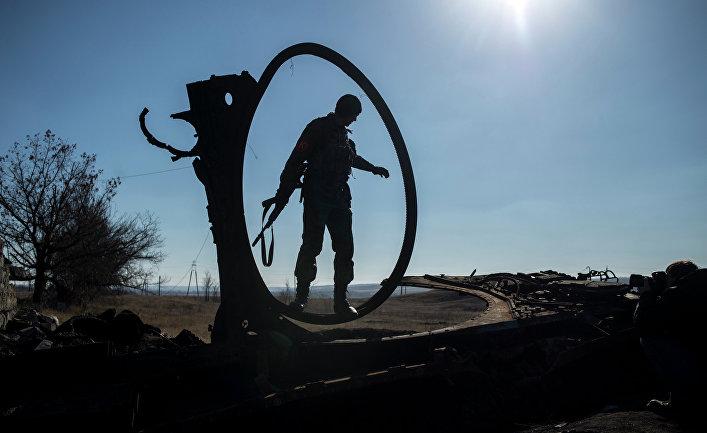 Боец ополчения ЛНР осматривает сгоревший украинский танк в поселке Новосветловка в Луганской области