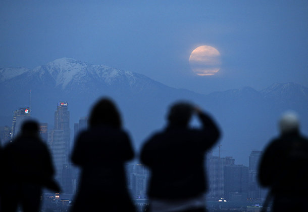 Люди наблюдают за суперлунием в пригороде Лос-Анджелеса