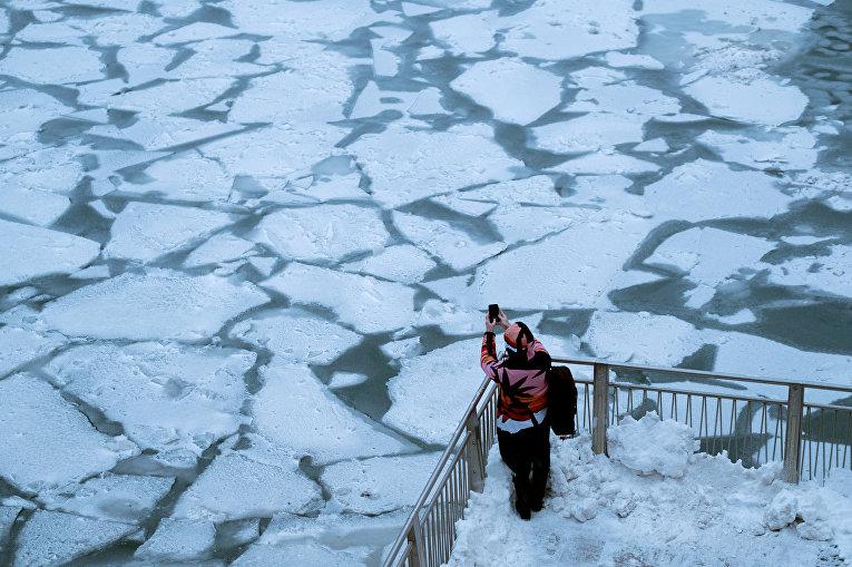 Прохожий фотографирует последствия снежного шторма и экстремально низких температур в Чикаго