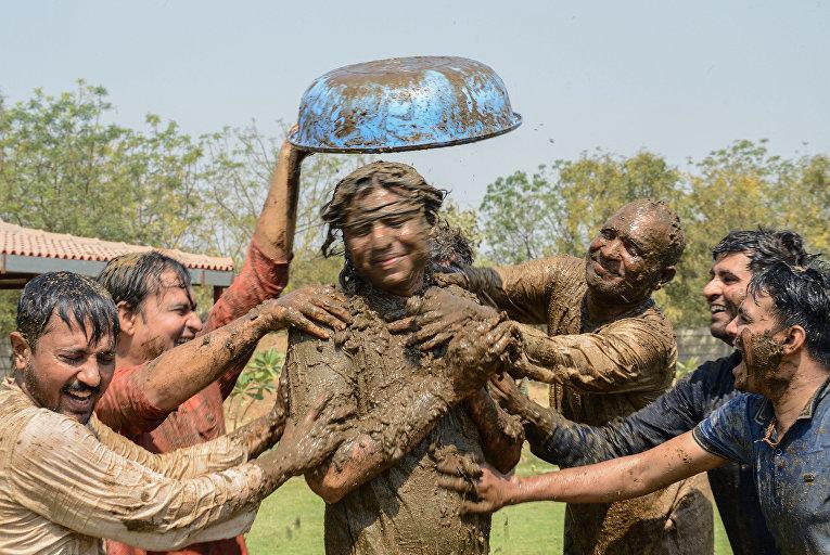 Индийские мужчины играют со свежим коровьим навозом