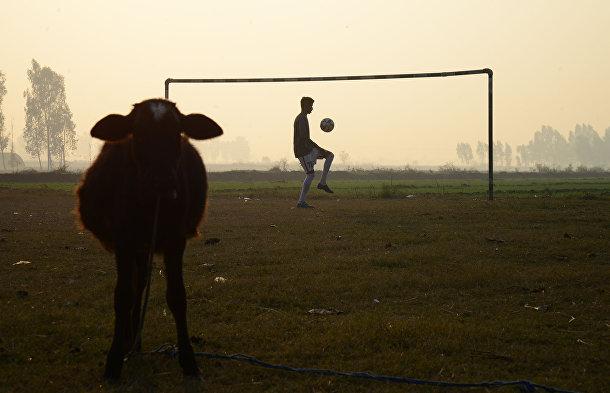 Индийский мальчик играет в футбол на окраине Джаландхара