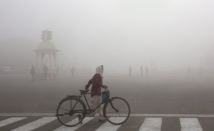 Велосипедист во время утреннего смога в Нью-Дели, Индия