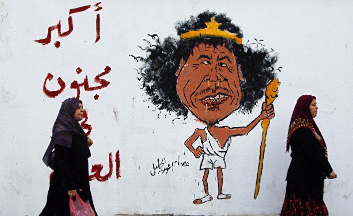 Женщины идут мимо граффити, изображающее Муаммара Каддафи