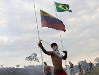 Протестующий во время столкновений с венесуэльскими солдатами у границы между Венесуэлой и Бразилией