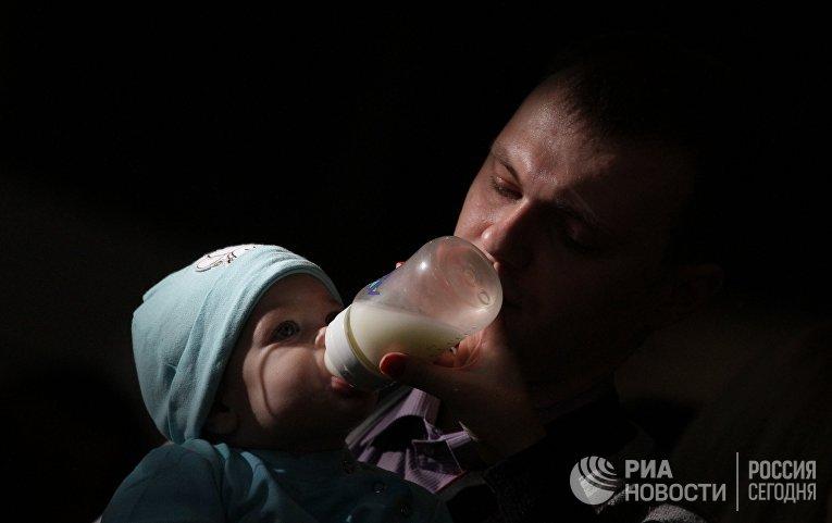 Отец кормит ребенка из из бутылочки на фестивале BabyFest в Сокольниках