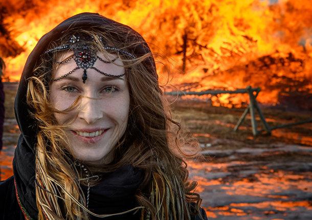 Девушка перед горящей крепостью Бастилия во время празднования Масленицы в Никола-Ленивце