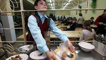 Школьник убирает за собой посуду в столовой