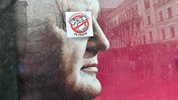 Наклейка с изображением свиньи на предвыборном плакате президента Украины Петра Порошенко в Киеве
