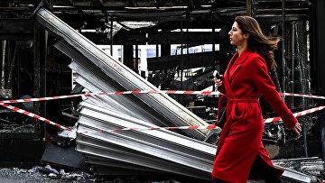 Женщина на фоне сгоревшего газетного киоска на Елисейских полях в Париже