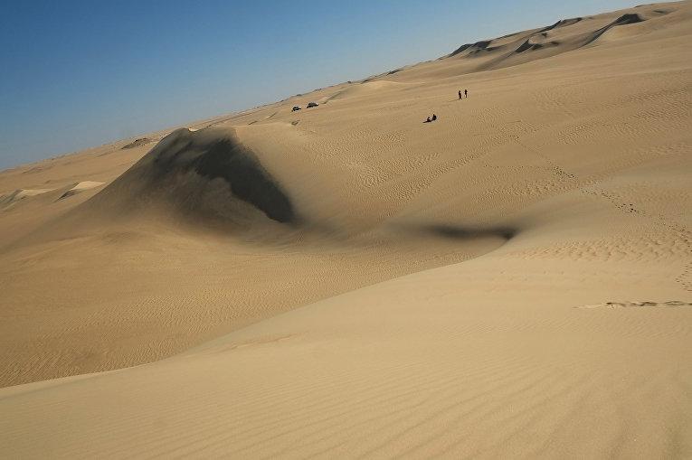 Люди у песчаной дюны в пустыне Египта