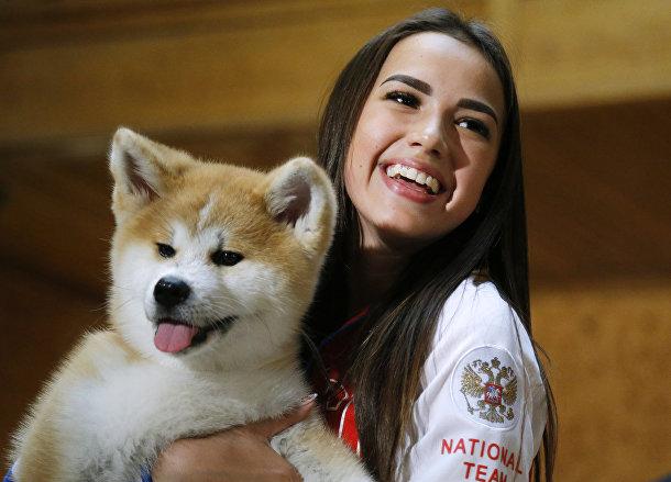 Алина Загитова держит щенка породы акита-ину