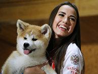 Алина Загитова держит щенка акита