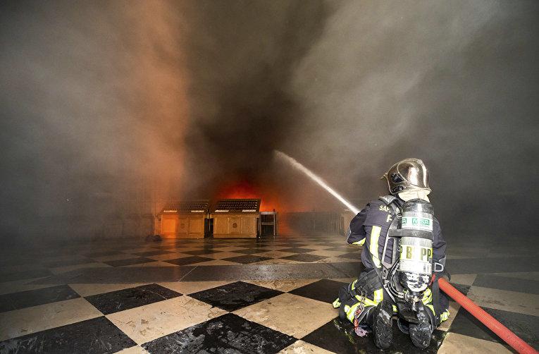 Пожарный тушит огонь в Соборе Парижской богоматери