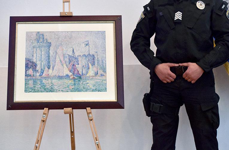 Украинский полицейский охраняет картину «Вход в порт Ла-Рошель» французского художника Поля Синьяка в Министерстве внутренних дел Украины в Киеве