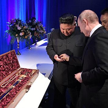 Путин дает лидеру КНДР Ким Чен Ыну монетку, получив от него в подарок меч