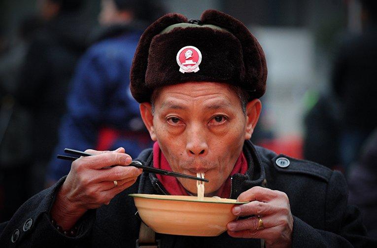 Человек ест лапшу в Шаошане, Китай