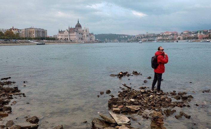 Молодой человек стоит на берегу Дуная в Будапеште
