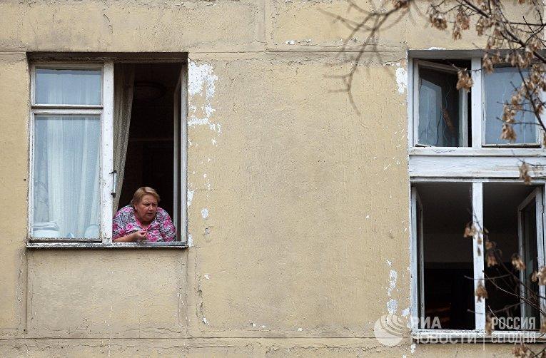 Женщина в окне пятиэтажного жилого дома