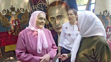 Пенсионеры Самары на фоне ковра с изображением президента России Владимира Путина