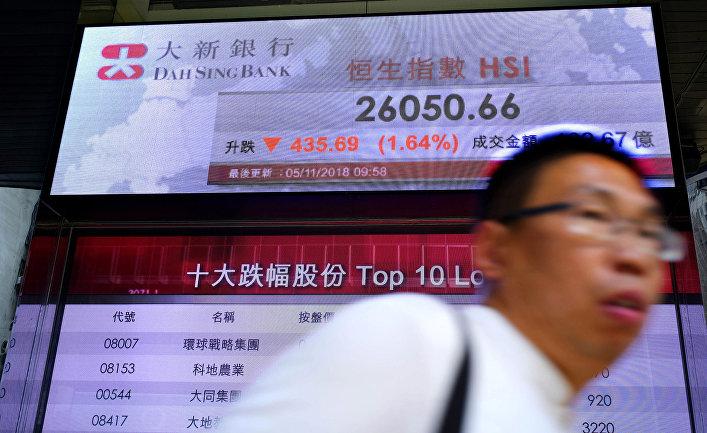 Прохожий идет мимо электронного табло, показывающего гонконгский индекс акций в Гонконге