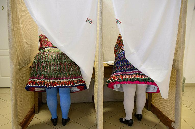 Женщины в народных костюмах во время голосования на избирательном участке в Буяке, Венгрия