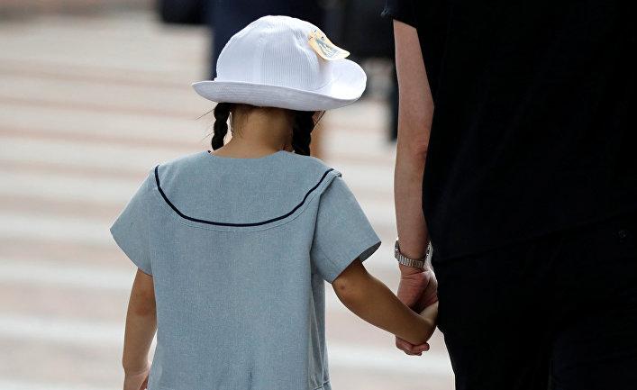 Девочку ведут в школу, ученики которой стали жертвами нападения в Кавасаки, Япония