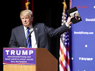 Дональд Трамп держит книгу