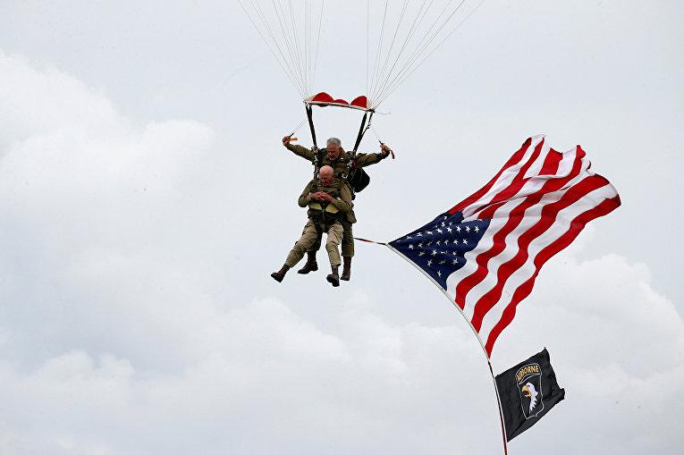 Ветеран-десантник Второй мировой войны США Том Райс прыгает во время памятного прыжка с парашютом над Карантаном на побережье Нормандии в преддверии 75-й годовщины D-Day
