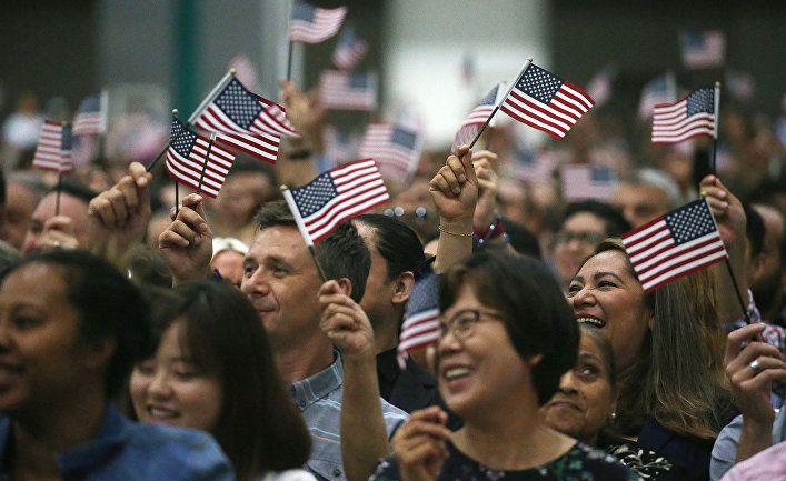 Люди машут американскими флагами на церемонии натурализации в Лос-Анджелесе