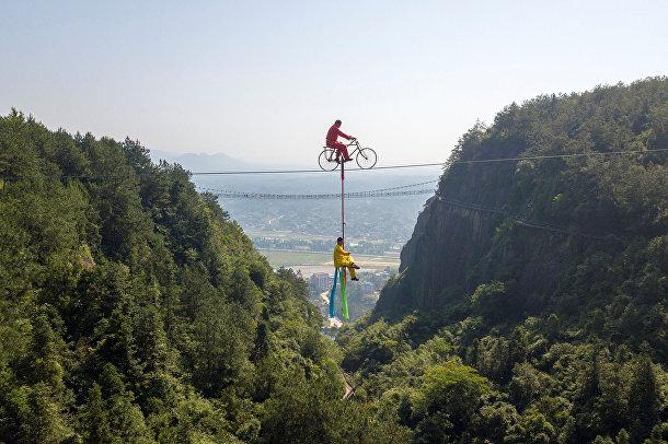 Выступление канатоходцев в Национальном геологическом парке Shiniuzhai в Юэян