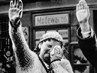 Женщина приветствует нацистского диктатора Адольфа Гитлера в 1938 году