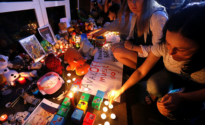 Портрет погибшего мальчика и свечи у здания департамента полиции в Киеве