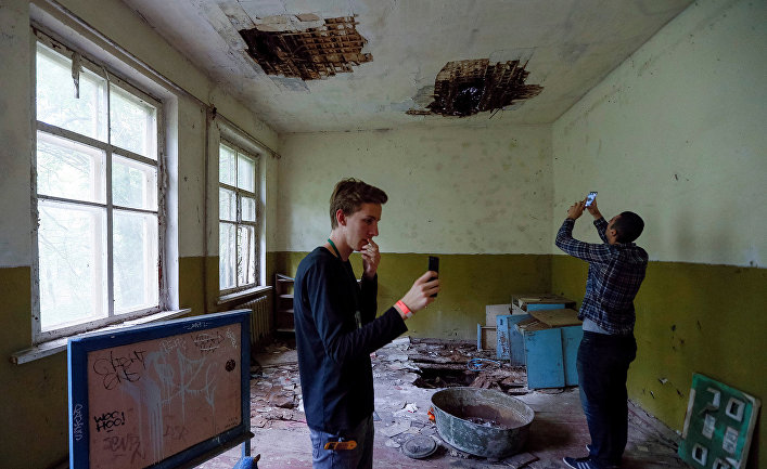 Туристы фотографируются в детском саду в заброшенном селе Копачи недалеко от Чернобыльской АЭС