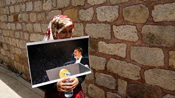 Женщина с портретом бывшего президента Египта Мохаммада Мурси на символической поминальной молитве в Стамбуле, Турция