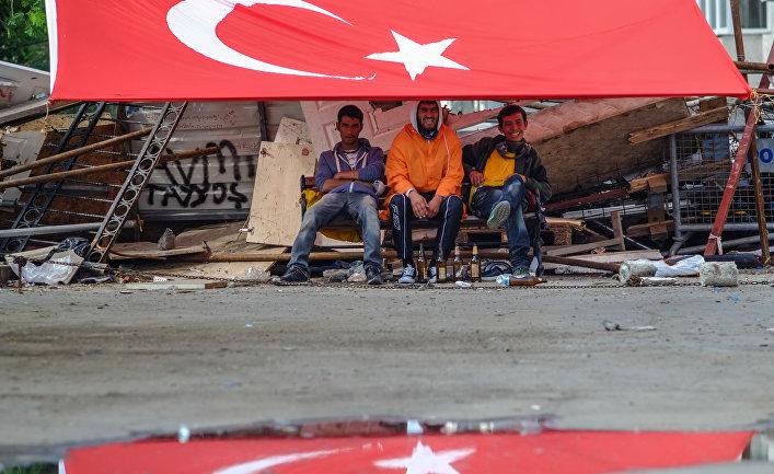 Молодые люди сидят под флагом Турции на площади Таксим в Стамбуле