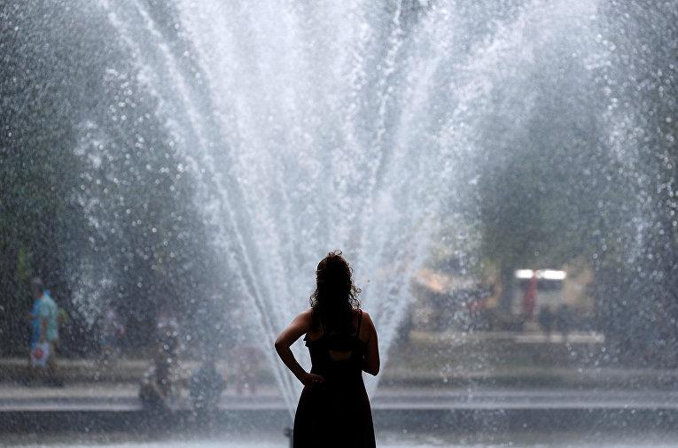 Женщина охлаждается возле фонтана в жаркий летний день в Брюсселе, Бельгия
