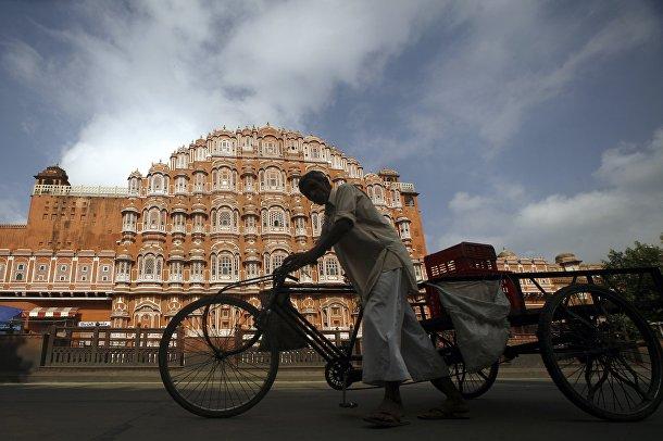 Велорикша проезжает мимо Дворца ветров в Джайпуре, Индия