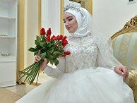 Модель демонстрирует свадебное платье в салоне магазина в Грозном