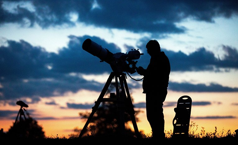 16 июля 2019. Люди настраивают телескопы, чтобы наблюдать частичное лунное затмение, Вена, Австрия