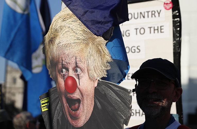 Сторонник ЕС с плакатом, изображающим Бориса Джонсона в виде клоуна во время демонстрации у Вестминстерского дворца в Лондоне